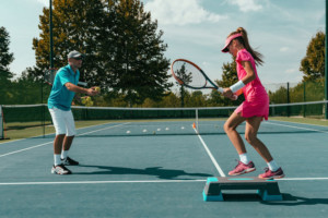 102156489 - tennis instructor with young girl on tennis training